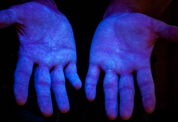 Bild 6. Fluoreszierendes Material unter UV-Licht, um den Deckungsgrad an den Händen des Menschen zu zeigen (Quelle www.glogerm.com)